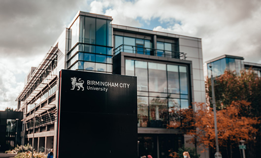 External shot of city south campus buildings and a sign with BCU logo.