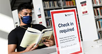 Student in library wearing face mask