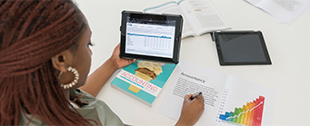 MSc Accounting and Finance Image 341x139 - Woman sat at desk with a tablet and accounting books