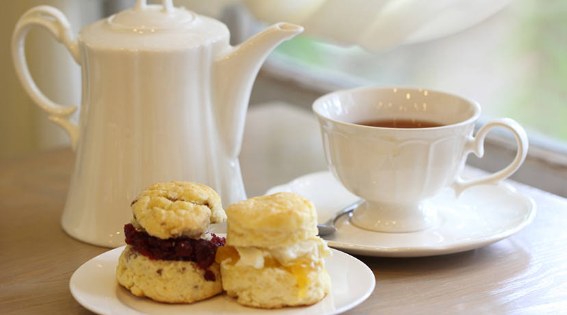 Teapot, cup of tea and scones