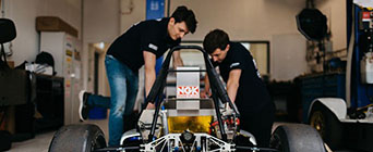 Engineering students working on a car