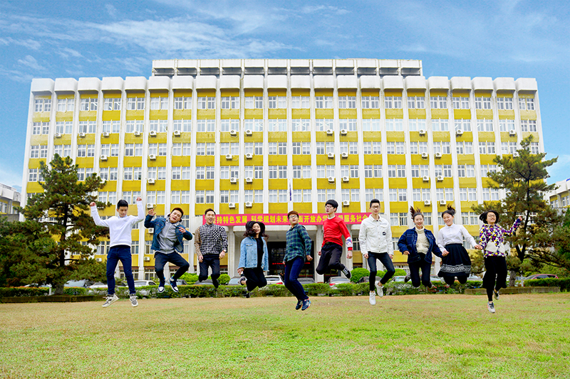 Students jumping outside main campus building