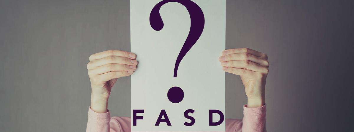woman holding sign saying FASD?