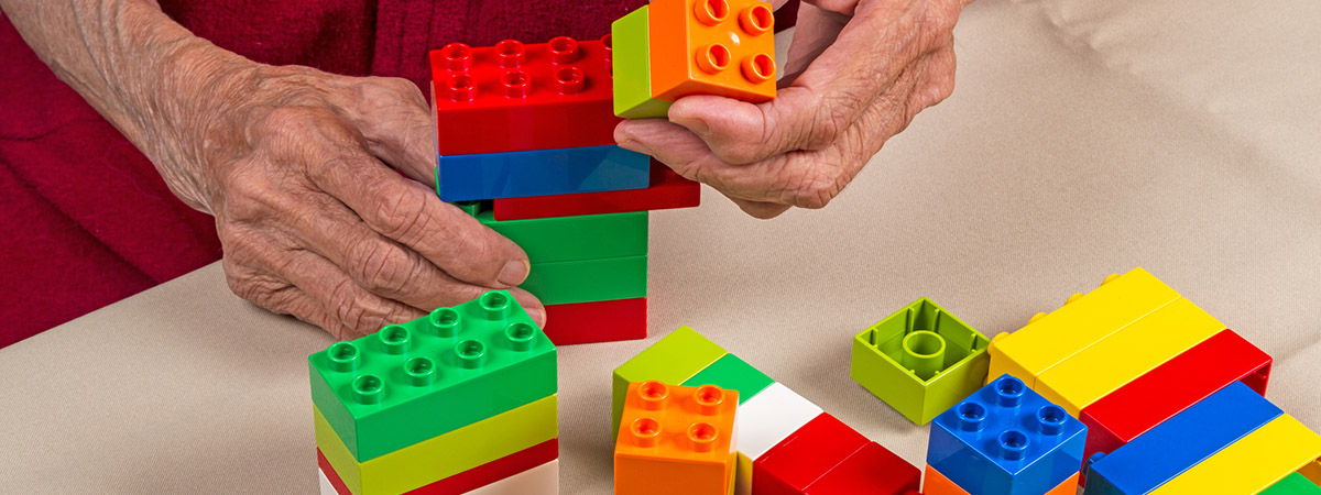An old man playing with Lego building blocks