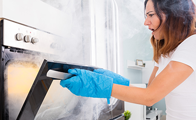 Woman opening oven to burnt food