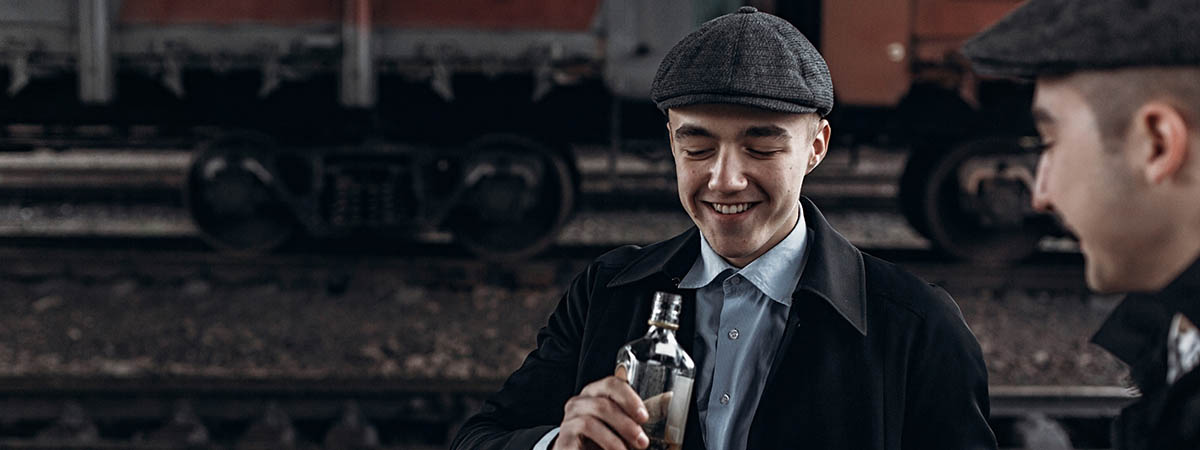 Peaky Blinders Response 1200x450 - Two men in peaky caps with alcohol