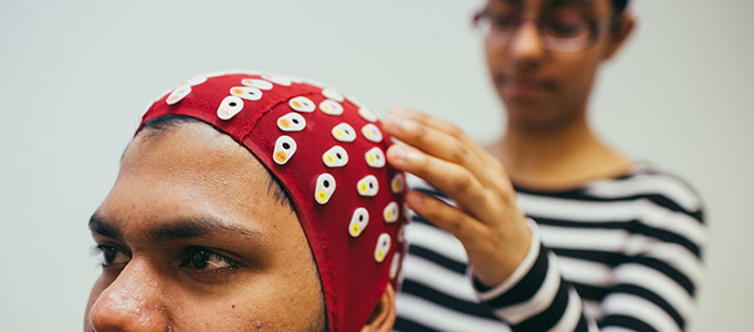 Psychology Labs 682x300 - Woman fitting a man with an EEG scanner