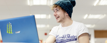 Photo of student on laptop smiling