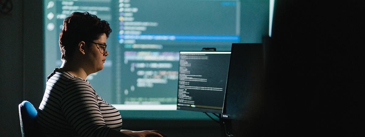 Student computer programming at desk