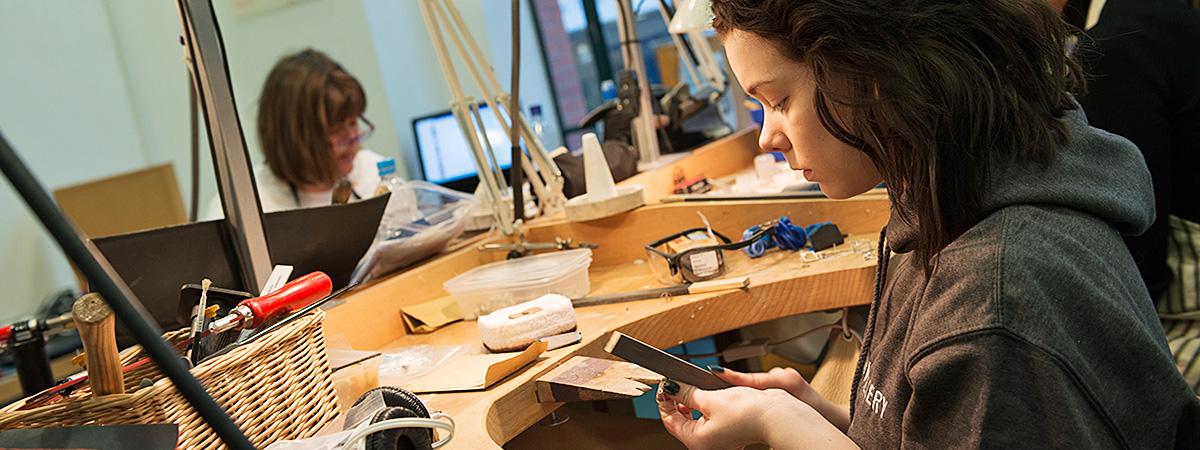 BCU Jewellery student filing a piece.
