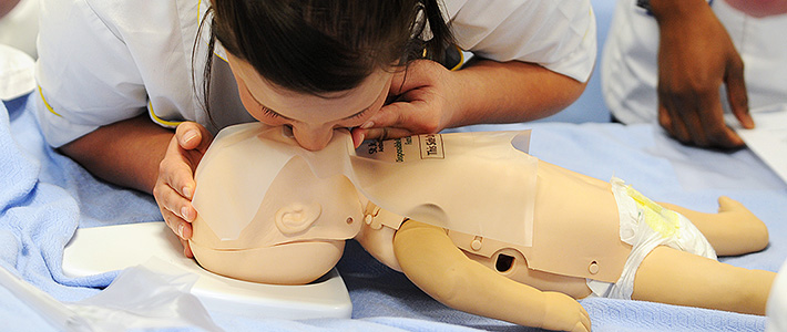 BCU Health Child Nursing student practicing mouth to mouth on a child dummy.