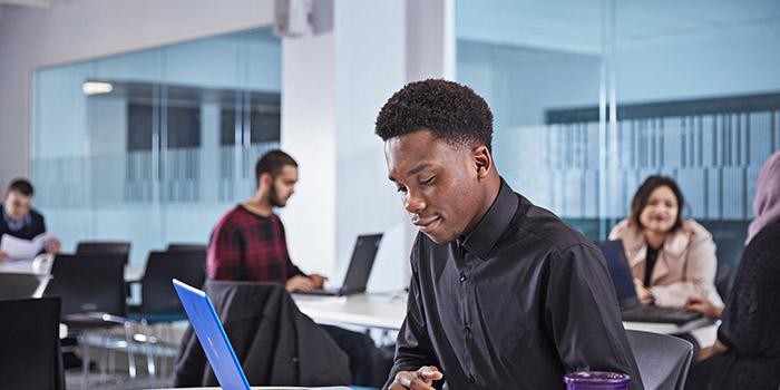 Why Study Economics 700x350 - Man on a laptop
